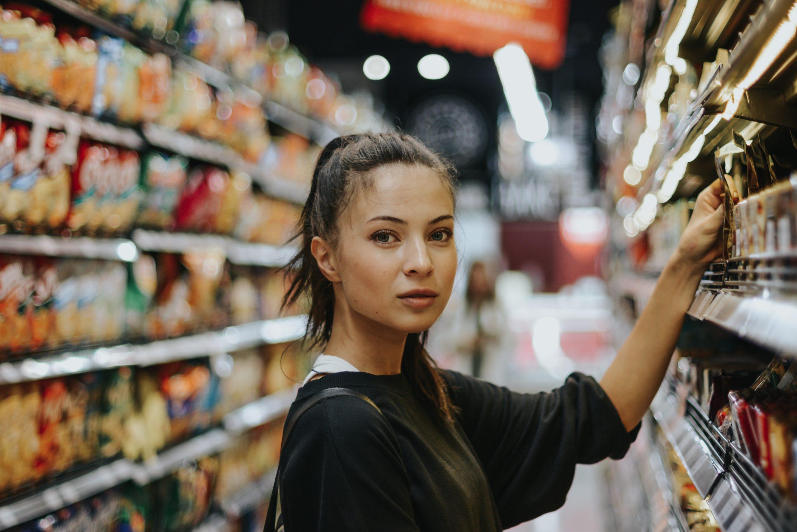 Frau im Laden vor einem Verkaufsregal